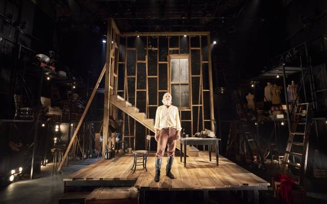 A man in a cream blouse, rust pants, and brown thigh-high boots stands alone on a stage. Behind him is the wooden frame of a wall, window, and staircase. The sides are cluttered with set pieces and props.