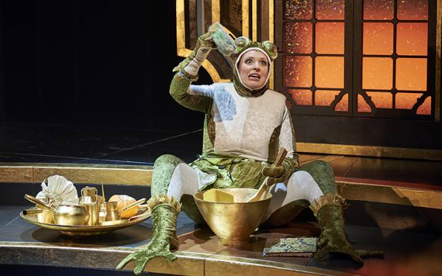 A white woman in a frog costume sits as she pours various ingredients into a gold mixing bowl. There is an air of comedy and farce.
