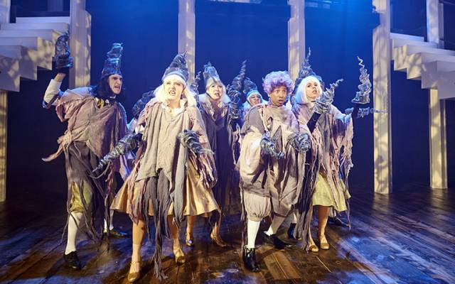 A group of 6 people of various genders and ethnicities are dressed in rags, resembling thorns. They all have angry or fearful facial expressions.