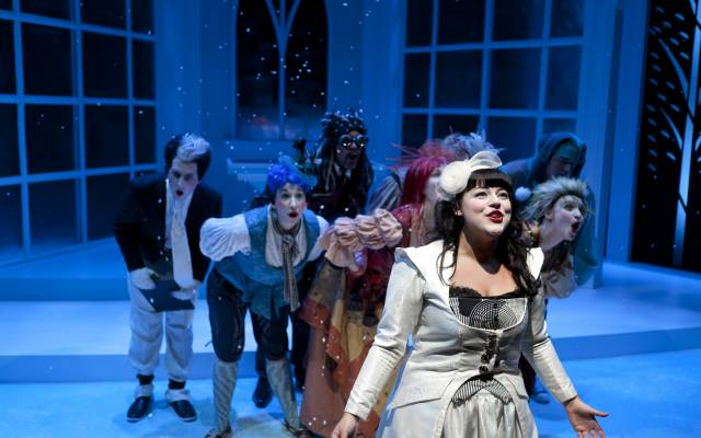 A white woman with long, black hair and bangs, dressed in a white suit dress, stands at the front of a pyramid of characters as they all sing in wonderment. Behind them is a blue-tinted set with three walls of windows.