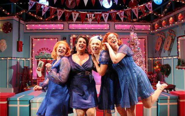 Four white women in blue dresses look gleeful in a room very decorated for the holidays.