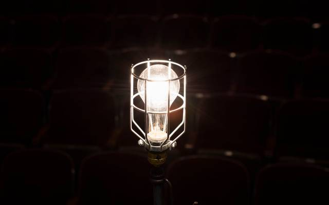 A bright ghost light shining in a dark theater with empty seats