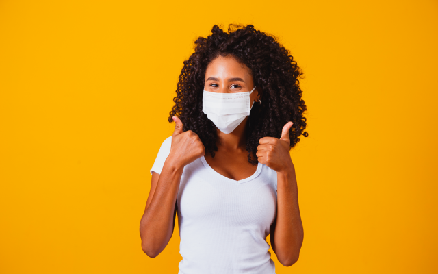black woman white t-shirt and face mask on against bright yellow background with two thumbs up